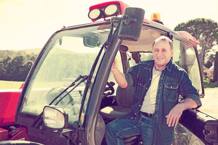 Portrait of senior male farmer sitting in tractor