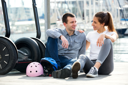 Positive young couple sitting near segways at sea front and smiling Фото со стока
