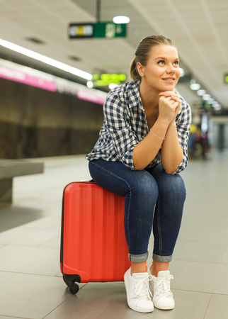 Young woman sitting on red suitcase while waiting for train at metro station