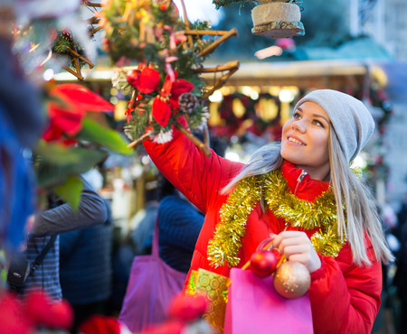 Young smiling woman choosing Xmas decoration on outdoor market