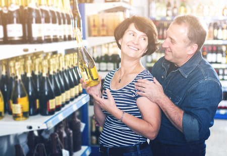 Smiling husband and wife selecting a vine at the grocery store Фото со стока - 117623614