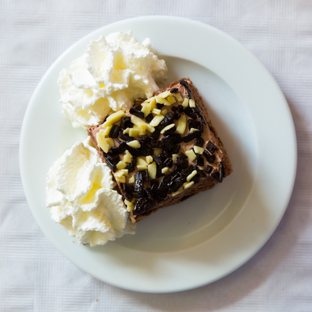 Portion of chocolate cake served with whipped cream