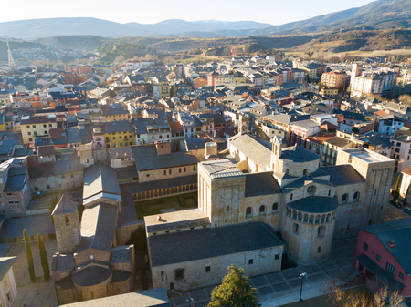 View from drone of medieval Cathedral of la Seu d'Urgell and residential area of city in sunny winter day, Catalonia, Spain