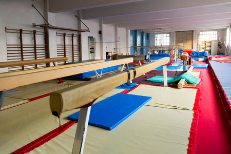 New acrobatic with gymnastic equipment – balance beams, bars and pommel horse Foto de archivo - 117625076