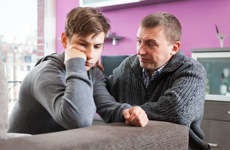 Father soothes teenager son after quarrel