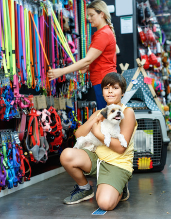 Smiling glad cheerful positive  tweenager boy embracing his puppy during family shopping in pet accessories shop Фото со стока
