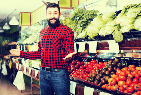 Happy adult male shop assistant demonstrating tomatoes in grocery shop