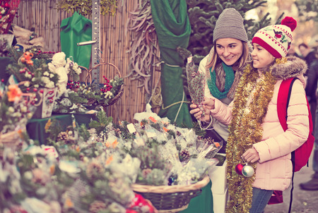 Young mom and girl buying flowers decoration at Christmas market