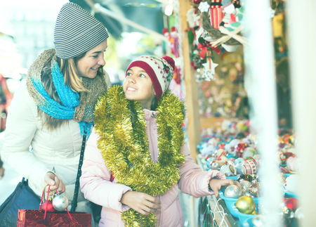 mother with little daughter buying decorations for Xmas at an open air market