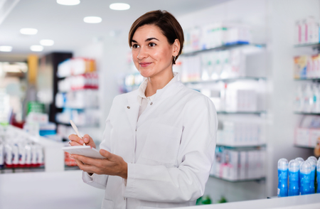 Diligent friendly smiling female pharmacist noting assortment of drugs in pharmacy