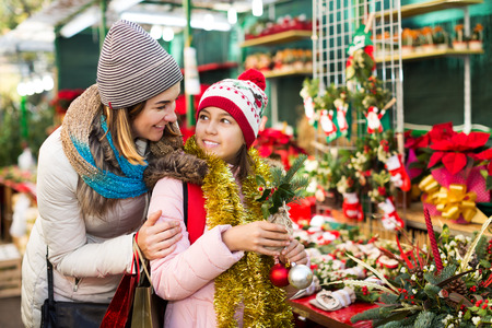 Happy girl with young mother choosing floral decoration for Xmas. Focus on girl