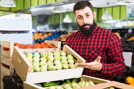 Smiling man seller choosing  pears in grocery shop Stockfoto