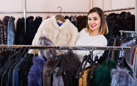 Young woman choosing white mink jacket in women's cloths store Archivio Fotografico