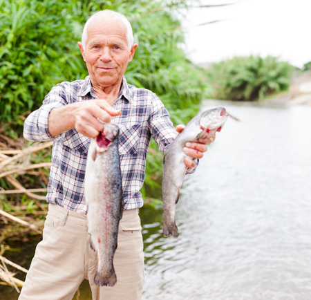 Portrait of smiling mature man holding fresh catch fish and angling gear at lakeside