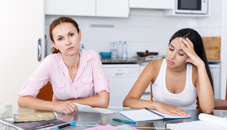 Teen girl learns badly, so her mother is unhappy, scene takes place in kitchen Stock Photo