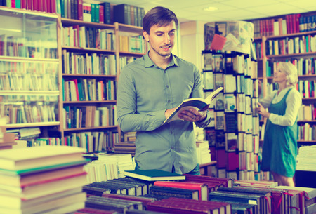 Young smiling man reading book while choosing it in book shop