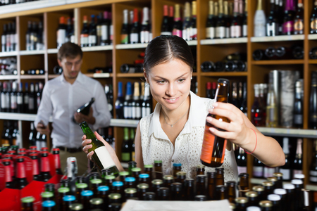 Smiling adult woman choosing bottle of alcohol beverage in wine shop Фото со стока - 117788299
