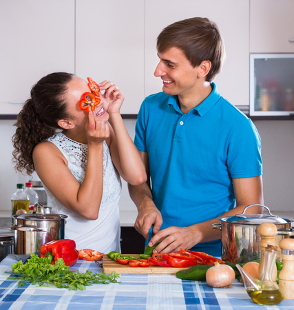 Young boyfriend helping wife to prepare healthy dinner