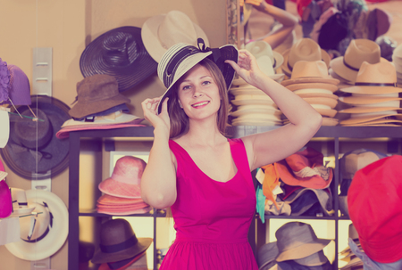 adult smiling russian woman try on hatinator hat  in shopping mall Stok Fotoğraf