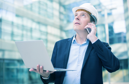 Smiling worker in helmet with laptop talking at mobile phone