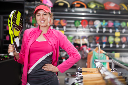 Young happy female is standing in uniform with new padel rocket in the speciality store.
