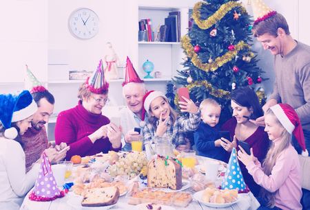 Large smiling family making numerous photos during Christmas dinner 스톡 콘텐츠 - 117832864
