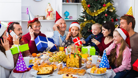 Large friendly smiling family enjoying their company during Christmas dinner