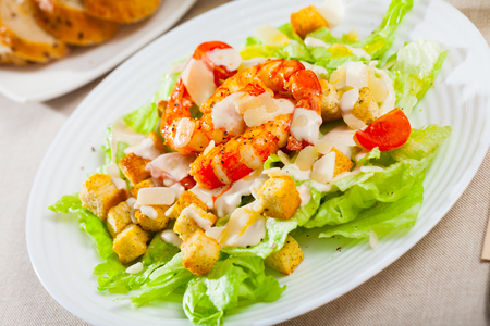 Image of fresh Caesar salad with shrimps on plate at restaurant Stock Photo