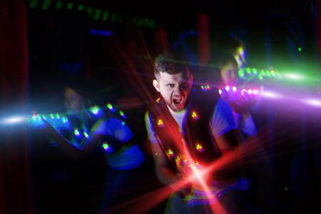 Portrait de joueur laser tag guy excité avec pistolet laser dans la chambre avec des faisceaux lumineux
