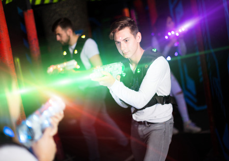 Portrait of guy in colored beams of laser guns during laser tag game on dark arena Stock Photo