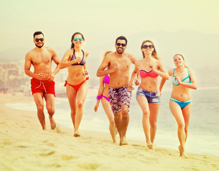 Happy people running at a beach