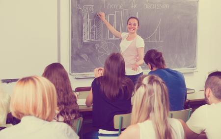 european girl standing at blackboard in classroom explains something