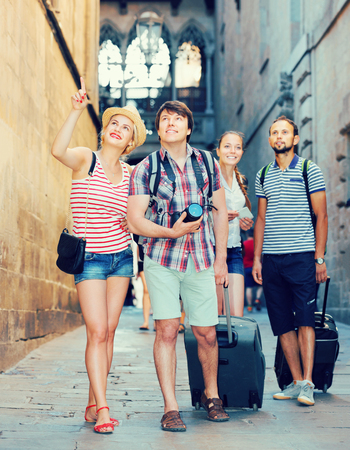 Group of european travelers walking at the street with luggage