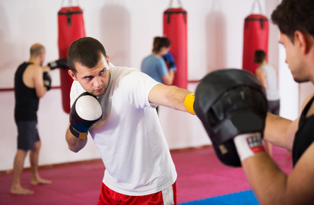Portrait of young active sportsmen competing in boxing gloves
