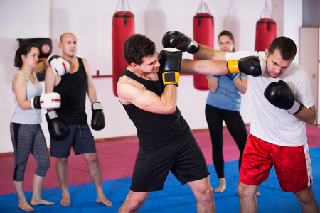 Portrait of young experienced sportsmen competing in boxing gloves