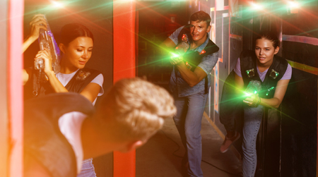 Portrait of active friends standing with laser guns during laser tag game in dark room Stock Photo