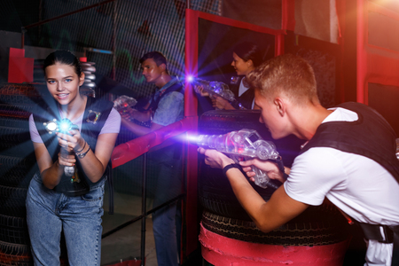smiling young friends holding colored laser guns during laser tag game in labyrinth Imagens