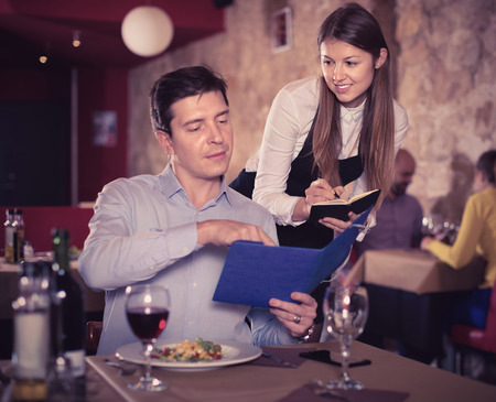 Hospitable positive smiling waitress helping handsome man with menu, taking order in restaurant