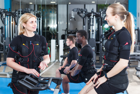 Two nice girls dressed EMS vests friendly talking while training in fitness gym Stock Photo