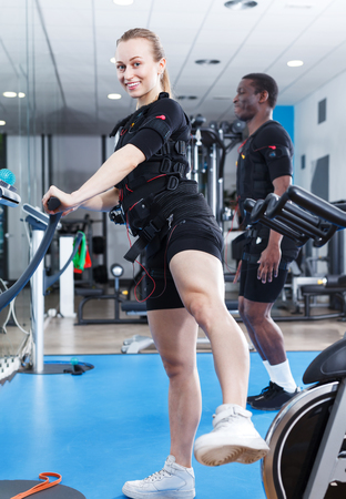 Young athletic woman in EMS suit exercising in modern training room