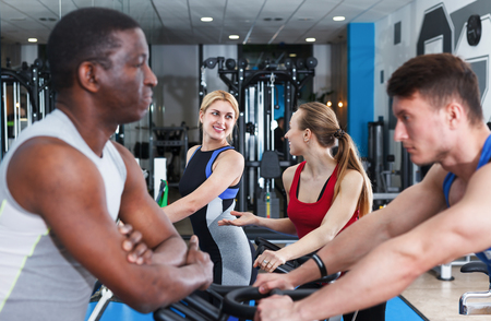 Young positive athletic people communicating during workout in training room