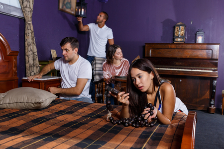 Young people looking at old wooden rosary while pursuing investigation in escape room with antique furniture Stock fotó