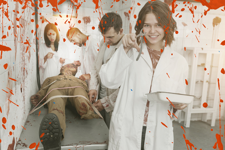 Portrait of happy girls with friends in quest room with bloody traces on walls and dead body on surgical table Stock Photo