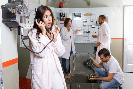 Young woman talking on telephone while her friends trying to find solution of conundrum in closed space of lost room-bunker