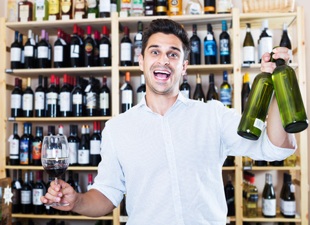 Cheerful man holding glass and bottle in winery section in store
