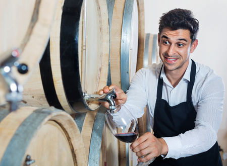 Glad man in uniform pouring red wine into glass in alcohol section with woods Reklamní fotografie