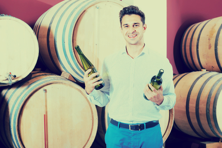 joyful man owner holding bottle of wine and standing in alcohol section with woods Reklamní fotografie