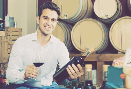 Positive male customer holding glass and bottle of wine in shop with woods Stock fotó