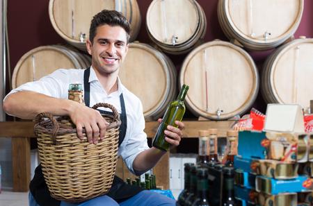positive male seller wearing apron with bottle in hands in cellar Reklamní fotografie