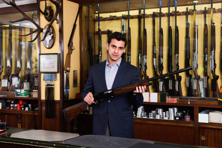Handsome positive glad adult male owner of hunting shop offering rifle